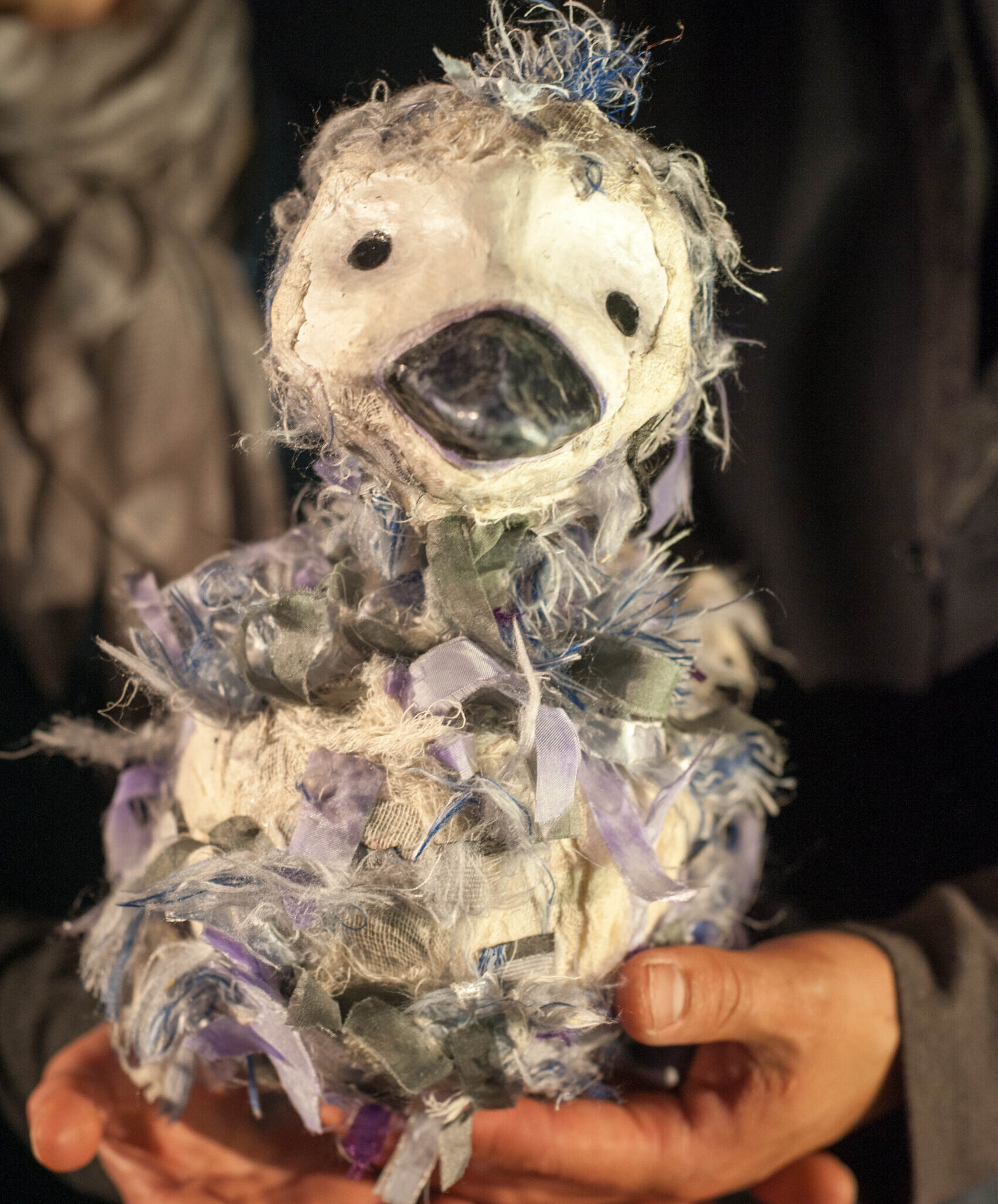 A bird puppet sits in a pair of hands