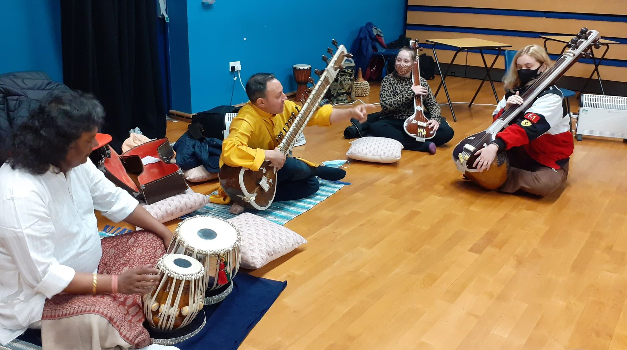4 people play Indian instruments in a workshop