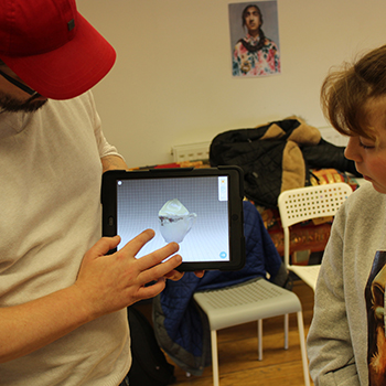 A man shows a girl AR software on a tablet computer