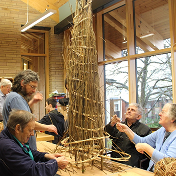 A group of older people weave a willow tree sat on a tabletop
