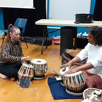 A girl and a man play tabla drums together