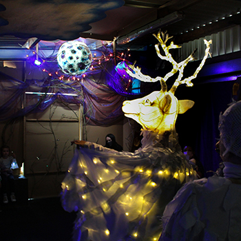 A man dressed as a stag looks to a illuminated moon
