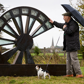 A man and his dog stand next to a sculpture of a wheel