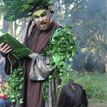 A man dressed in leaves reads from a book