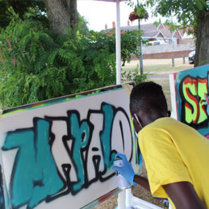 A young man painting a graffiti artwork