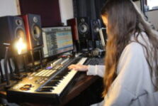 A young woman plays a keyboard in a recording studio