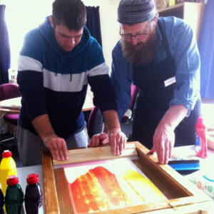 Two men drag ink across a screen to create a print