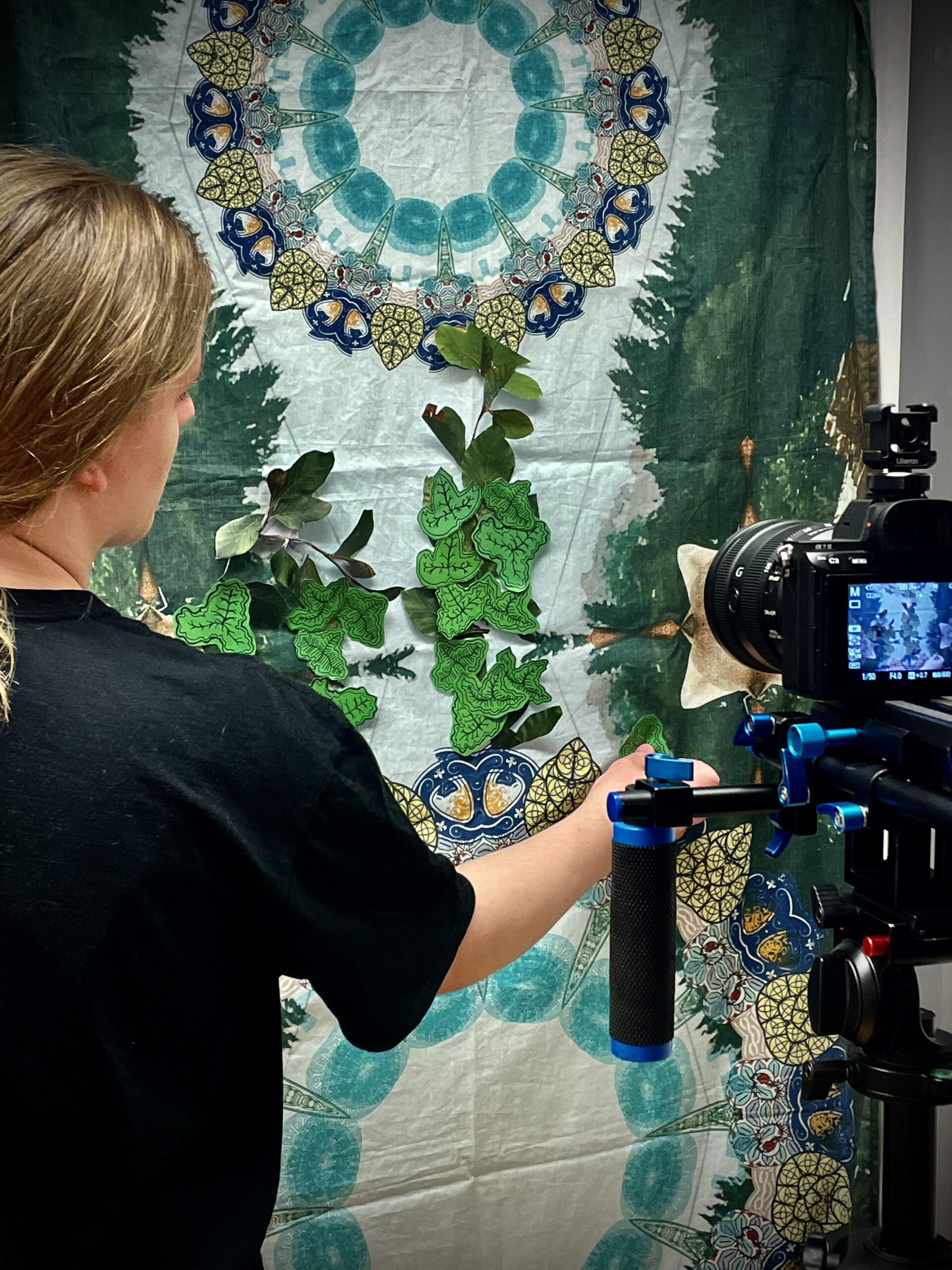 A young participant sticks hand drawn leaves to a colourful background whist being filmed with a camera.