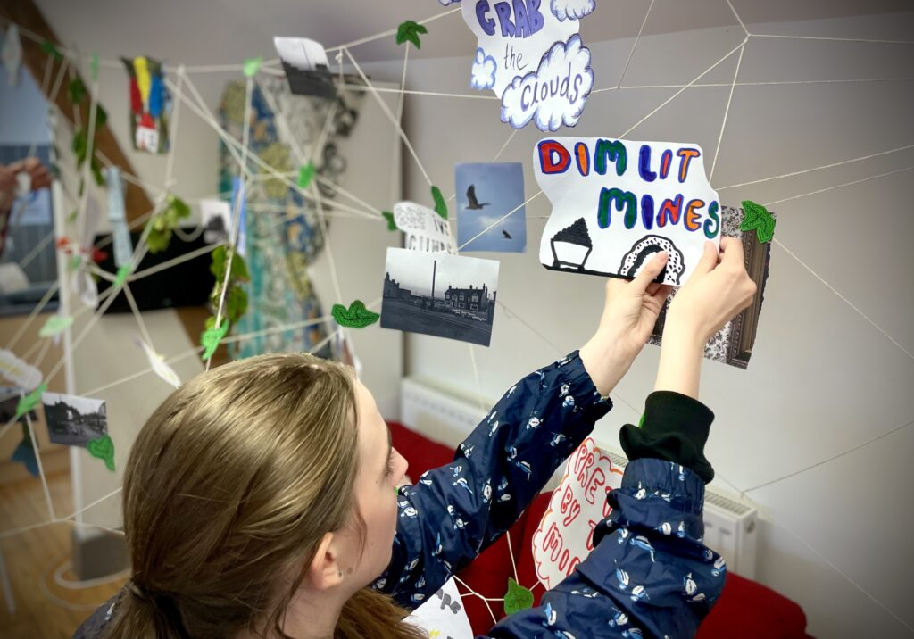 A young woman pins a hand-drawn picture to a piece of string in an installation. The picture reads 'Dim lit mines'.