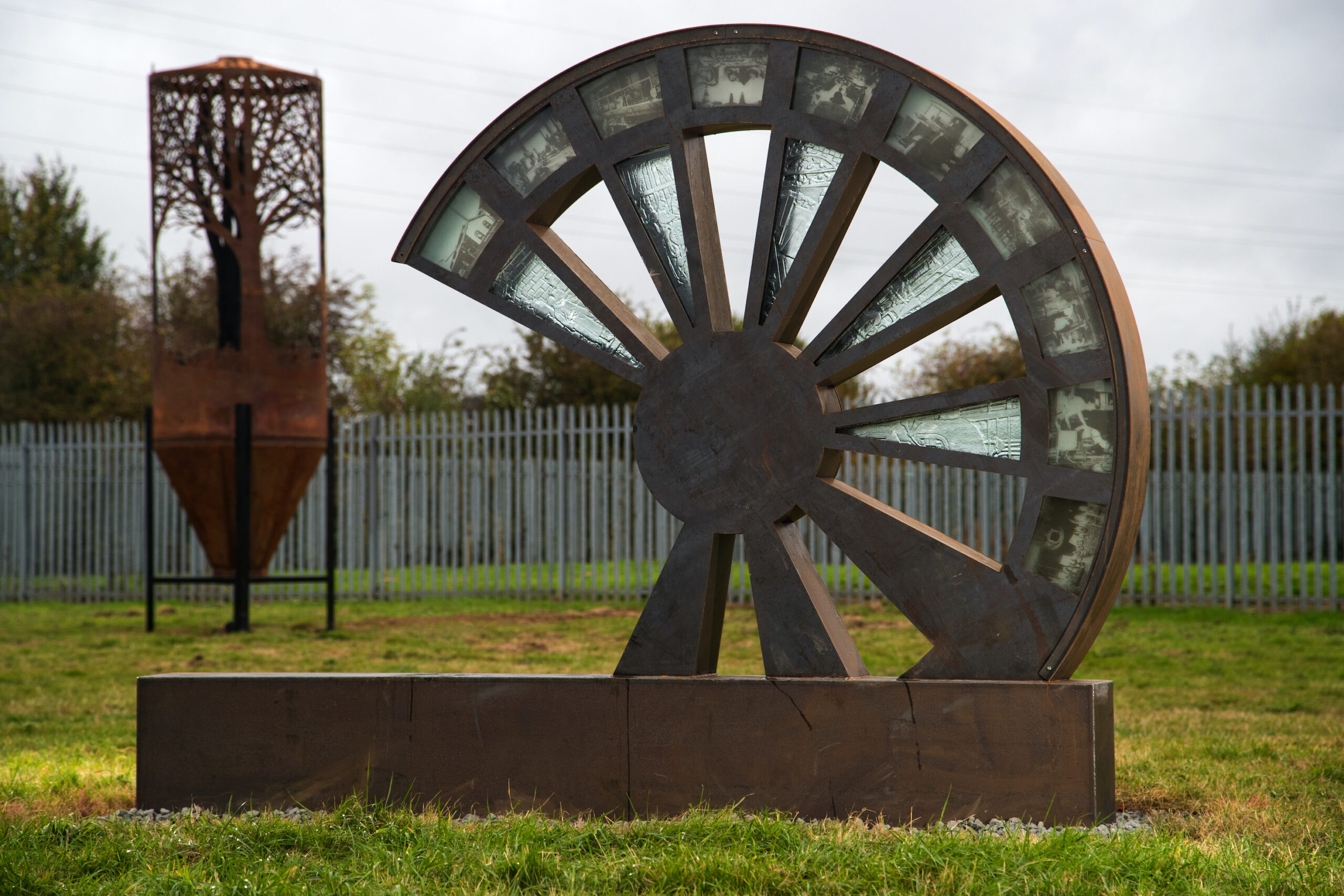 A sculpture made of steel and glass in the shape of a wheel