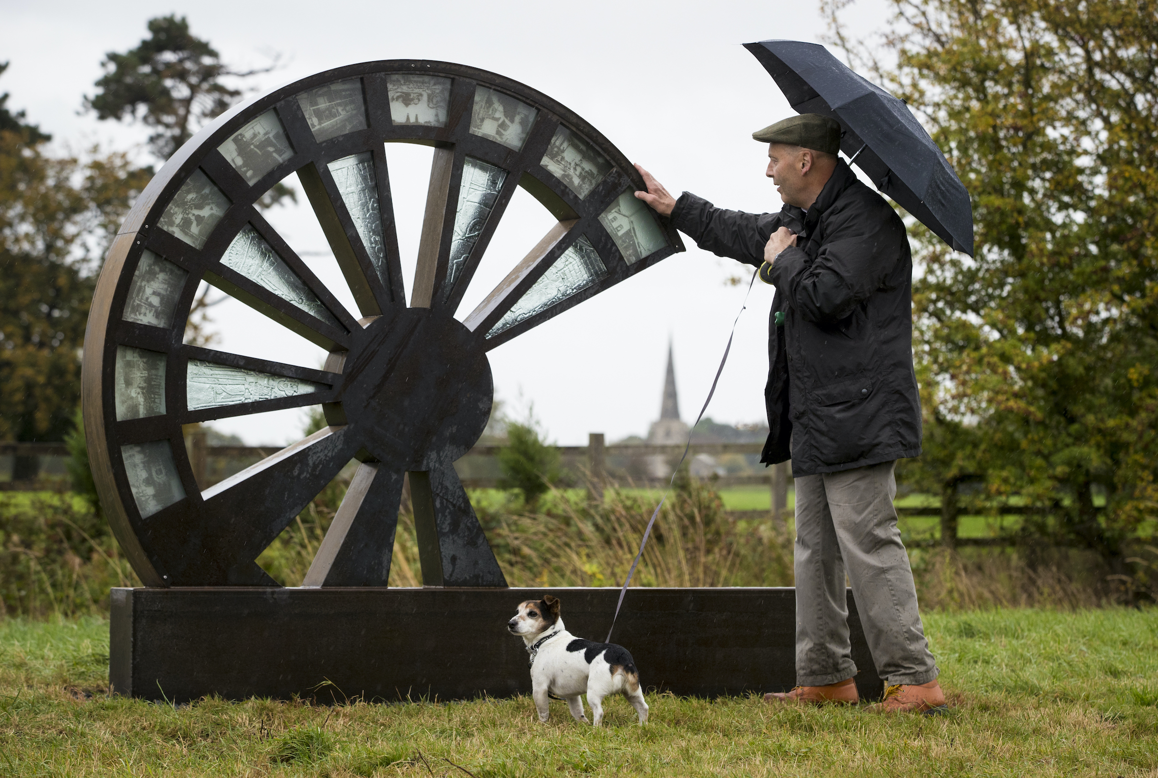 A man and his dog stand next to a wheel shaped sculpture